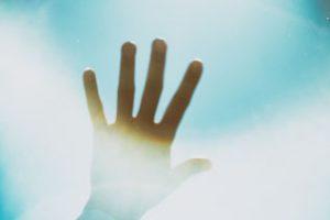 太陽に手をかざした写真